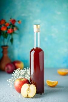 Vorderansicht roter apfelessig auf blauem wandnahrungsmittelgetränkfruchtalkoholwein saurer farbsaft