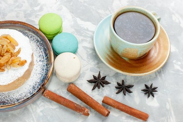Vorderansicht runder kleiner kuchenzucker, der mit rosinentee und französischen macarons auf weißem schreibtischzuckersüßkekskuchen-sahnetorte pulverisiert wird