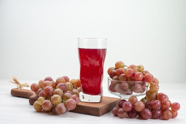 Vorderansicht saure frische trauben mit saft auf weißem schreibtischfrucht frischem mildem saftgetränk