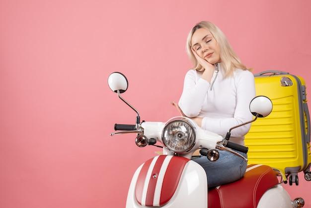 Vorderansicht schläfrige junge dame auf moped, das augen schließt