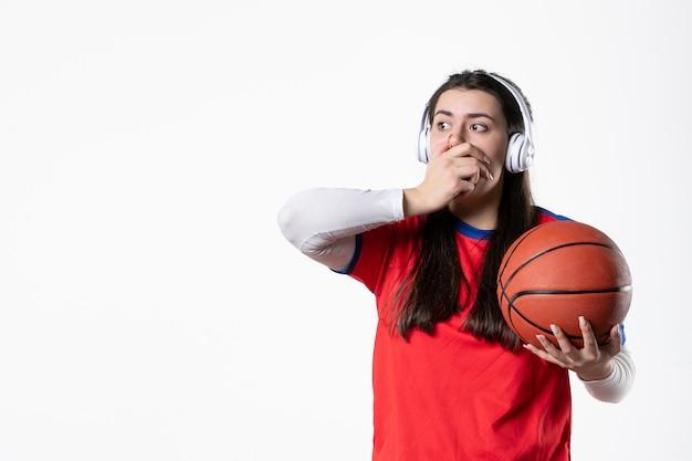 Vorderansicht schockierte junge frau in sportkleidung mit basketball