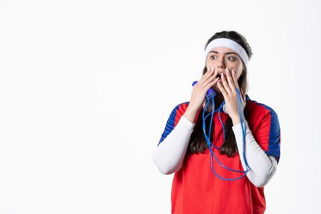 Vorderansicht schockierte junge frau in sportkleidung mit springseilen