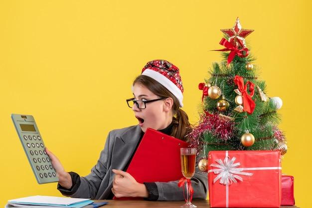 Vorderansicht schockiertes mädchen mit weihnachtshut, das am tisch sitzt und weihnachtsbaum und geschenkcocktail des rechners betrachtet