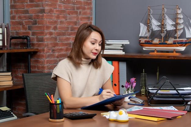 Vorderansicht schöne geschäftsfrau, die dokumente am schreibtisch im büro überprüft