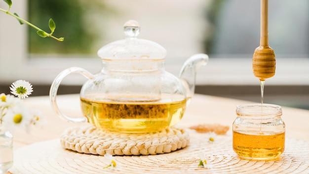 Vorderansicht schöpflöffel über honigglas und teekanne