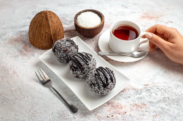 Vorderansicht schokoladenkuchen mit tasse tee auf dem hellweißen oberflächenschokoladenkuchenkekszuckersüßkeks