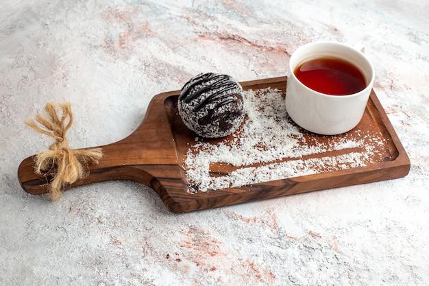 Vorderansicht schokoladenkuchen mit tasse tee auf dem weißen schreibtisch schokoladenkuchen keks zucker süße kekse