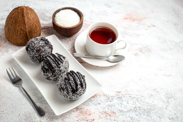 Vorderansicht schokoladenkuchen mit tasse tee auf weißen schreibtisch schokoladenkuchen keks zucker süße kekse