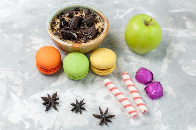 Vorderansicht schokoladenplätzchen-nachtisch mit französischen macarons und apfel auf hellweißem schreibtischplätzchen süßer backzuckerkuchenkeks