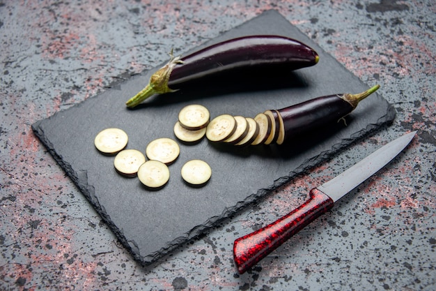 Vorderansicht schwarze auberginen geschnitten und ganz auf schneidebrett blauen hintergrund