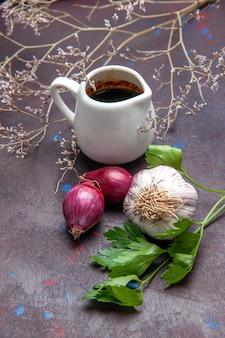Vorderansicht schwarze soße mit zwiebeln auf dunklem oberflächensalat rohe pflanzennahrung