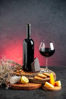 Vorderansicht schwarze weinflasche rotwein in glaskäse geschnittene zitronenstücke dunkler schokolade auf holzbrettern getrockneter blumenzweig auf rotem tisch