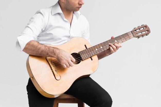 Vorderansicht sitzender mann, der die gitarre spielt