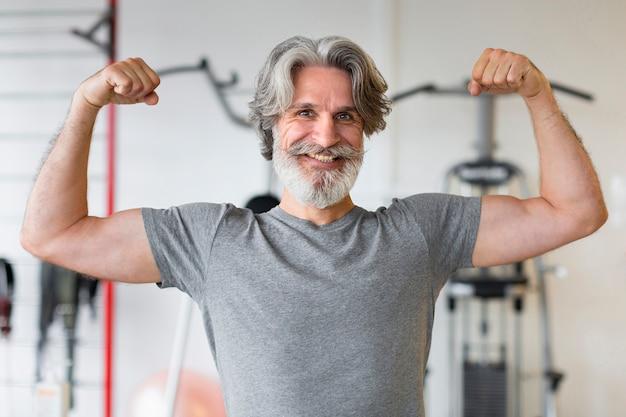 Vorderansicht smiley-mann im fitnessstudio
