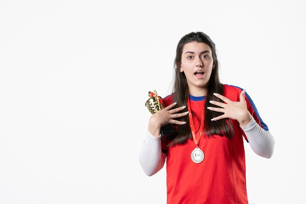 Vorderansicht spielerin in sportkleidung mit medaille und goldenem pokal