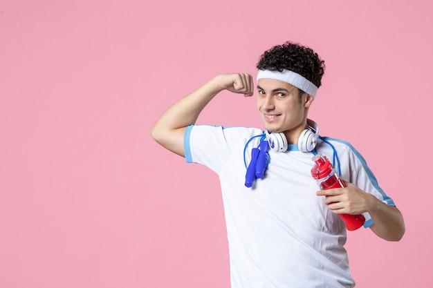 Vorderansicht starker männlicher fitnessmann mit kopfhörern und wasserflasche