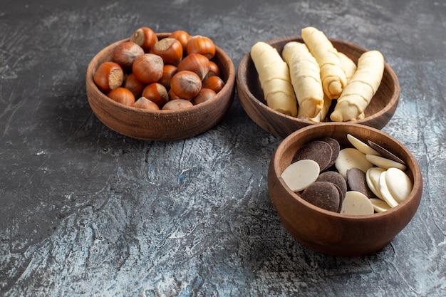 Vorderansicht süße bagels mit keksen und nüssen auf dunklem hintergrund
