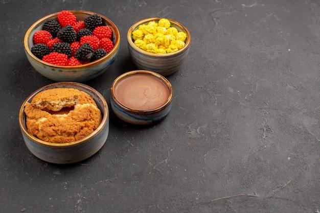 Vorderansicht süße bonbons mit keksen auf dunklem hintergrund bonbonfarbener konfitüre-tee