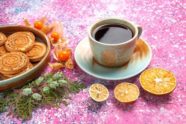 Vorderansicht süße kekse köstliche kleine kekse mit physalisierungen und tee auf hellrosa schreibtisch.
