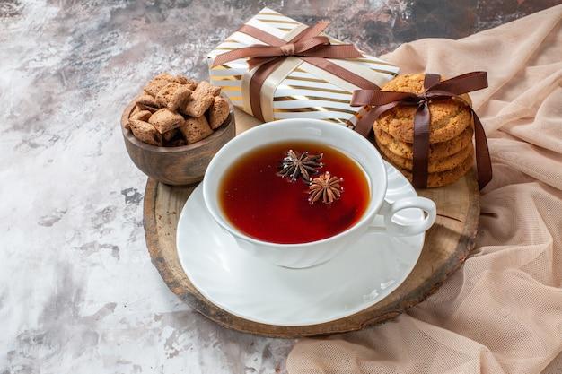 Vorderansicht süße kekse mit geschenk und tasse tee auf heller hintergrundfarbe kuchenteeplätzchen süßes gebäck kuchenzucker