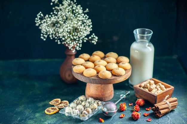 Vorderansicht süße kekse mit milch auf der dunkelblauen oberfläche