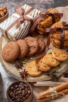 Vorderansicht süße kekse mit nüssen und geschenken auf heller hintergrundfarbe zuckerteekuchen süßes tortengebäck