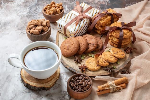 Vorderansicht süße kekse mit nüssen und geschenken auf heller hintergrundfarbe zuckerteekuchenplätzchen süßes tortengebäck