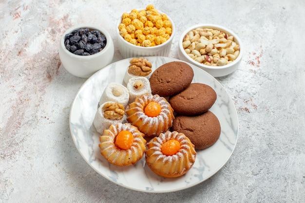 Vorderansicht süße kekse mit süßigkeiten und nüssen auf dem weißen raum
