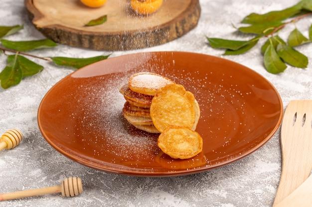 Vorderansicht süße köstliche pfannkuchen innerhalb der braunen platte auf dem süßen dessert der grau-hellen oberfläche pfannkuchen-mahlzeit mahlzeit