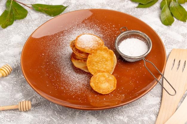 Vorderansicht süße köstliche pfannkuchen innerhalb der braunen platte auf dem süßen nachtisch der pfannkuchenmahlzeit der grau-hellen oberfläche