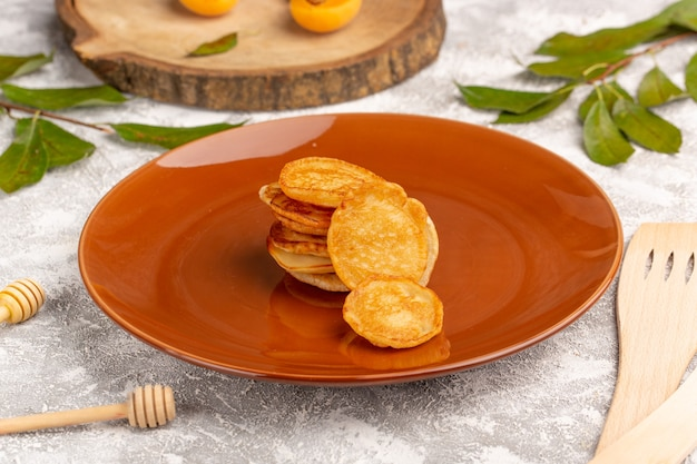 Vorderansicht süße köstliche pfannkuchen innerhalb der braunen platte auf dem süßen nachtisch des grau-hellen schreibtischpfannkuchen-essensmahls
