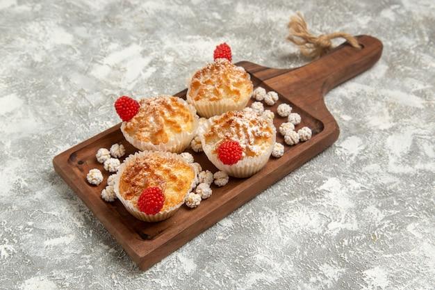 Vorderansicht süße kuchen mit bonbons auf der weißen oberfläche