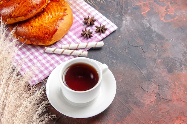 Vorderansicht süße kuchen mit tasse tee auf dunklem tischkuchen kuchen gebäck süß