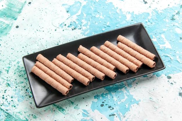 Vorderansicht süße lange kekse in schwarzer kuchenform auf blauer oberfläche
