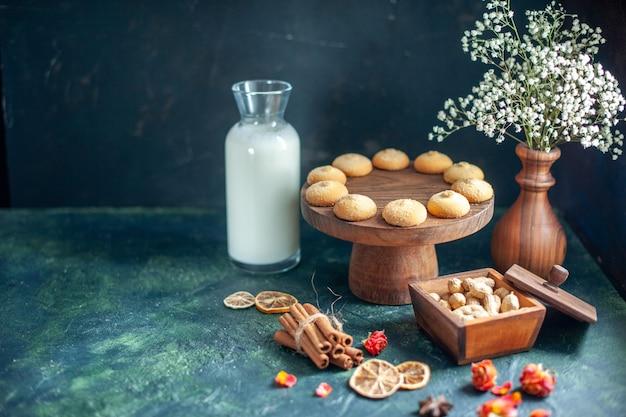 Vorderansicht süße leckere kekse mit milch und nüssen auf der dunkelblauen oberfläche