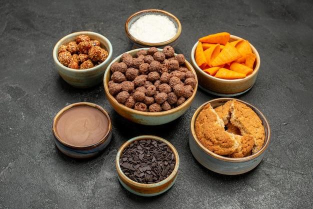 Vorderansicht süße nüsse mit kakaoflocken und cips auf dunklem hintergrund snack milchmahlzeit frühstücksfarbe