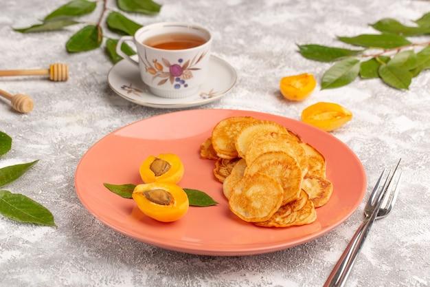 Vorderansicht süße pfannkuchen in pfirsichplatte mit aprikosen und tee auf dem grauen schreibtisch pfannkuchen essen mahlzeit süßes dessert obst