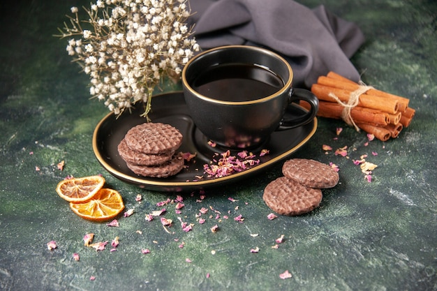 Vorderansicht tasse tee in schwarzer tasse und teller mit keksen auf dunkler oberfläche farbe zucker frühstück dessert kuchen keks zeremonie