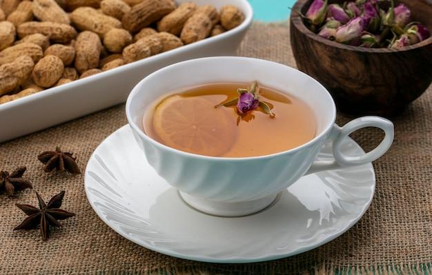 Vorderansicht tasse tee mit einer zitronenscheibe und erdnüssen mit getrockneten blumen