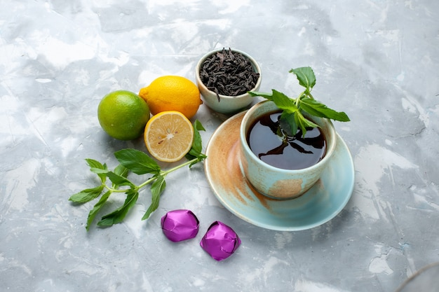 Vorderansicht tasse tee mit frischen zitronensüßigkeiten und getrocknetem tee auf leuchttisch, teefrucht zitrusfarbe