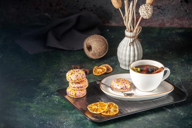 Vorderansicht tasse tee mit kleinen süßen keksen in teller und tablett auf dunkler oberfläche zeremonie glas süße frühstückstorte zuckerfarbe