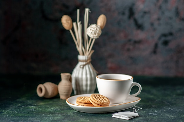 Vorderansicht tasse tee mit kleinen süßen keksen in weißer platte auf dunkler oberfläche farbzeremonie frühstück morgen foto glas trinken zucker