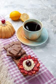 Vorderansicht tasse tee mit kuchen zitrone und schokoriegel auf dem weißen schreibtisch kuchen süße zuckerschokolade