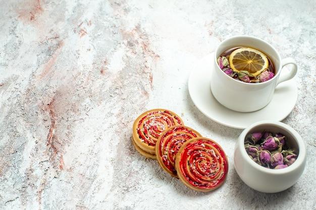 Vorderansicht tasse tee mit leckeren zuckerkeksen auf weißem raum