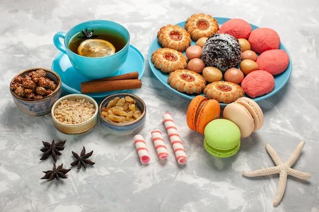 Vorderansicht tasse tee mit macarons kekse und kuchen auf weißer oberfläche keks keks zucker süße kuchen süßigkeiten