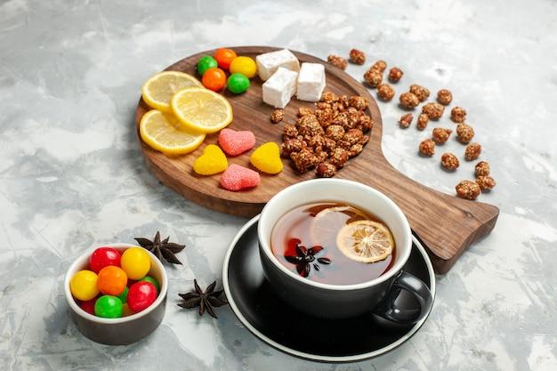 Vorderansicht tasse tee mit nüssen und süßigkeiten auf weißer oberfläche
