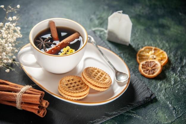 Vorderansicht tasse tee mit süßen keksen auf dunkler oberfläche brot getränk zeremonie glas süßes frühstück morgen zuckerkuchen farbfotos