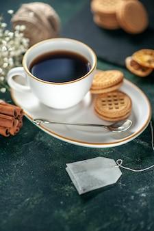 Vorderansicht tasse tee mit süßen keksen auf dunkler oberfläche brot getränk zeremonie süßes frühstück morgen foto zucker kuchen glas farbe