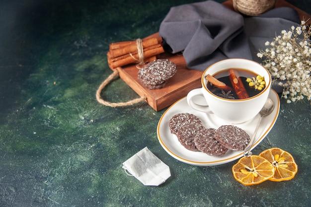 Vorderansicht tasse tee mit süßen schoko-keksen in teller und tablett auf dunkler oberfläche zucker zeremonie glas frühstückstorte dessert farbe süß