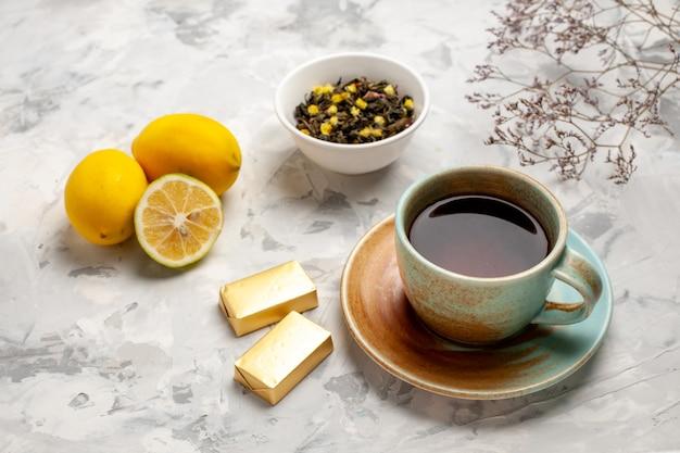 Vorderansicht tasse tee mit süßigkeiten und zitrone auf weißem raum
